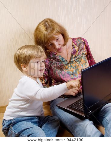 Mother And Her Son Siting On A Floor Looking The Laptop