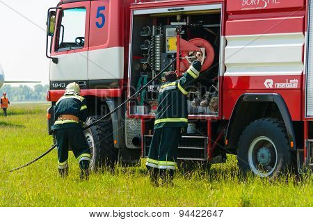 BORYSPIL, UKRAINE - MAY, 20, 2015: Firefighter lifted the Red hose after training put off the fire a