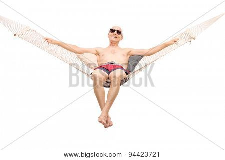 Relaxed senior man in red swim trunks lying on a comfortable hammock isolated on white background