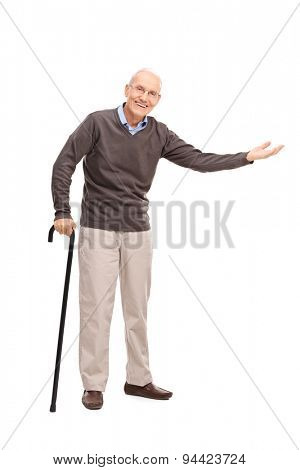 Full length portrait of a senior with a cane smiling and gesturing with his hand isolated on white background