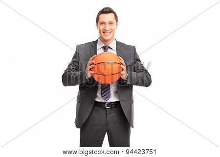 Young cheerful businessman holding a basketball and looking at the camera isolated on white background