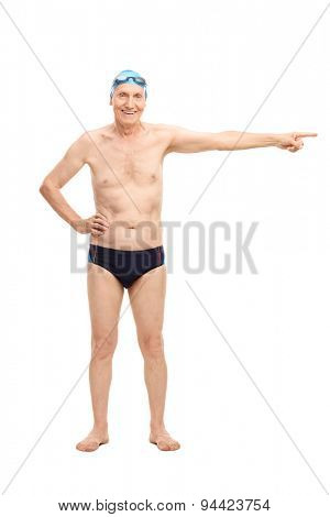 Full length portrait of a senior man in black swim trunks pointing with his hand towards right and looking at the camera isolated on white background