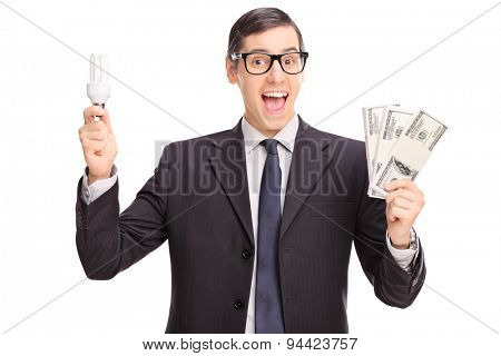 Cheerful young man holding an energy saving light bulb and three stacks of money isolated on white background