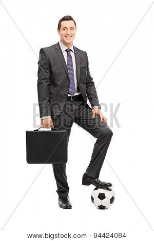 Full length portrait of a young cheerful businessman in a black suit holding a suitcase and posing with a football under his foot isolated on white background