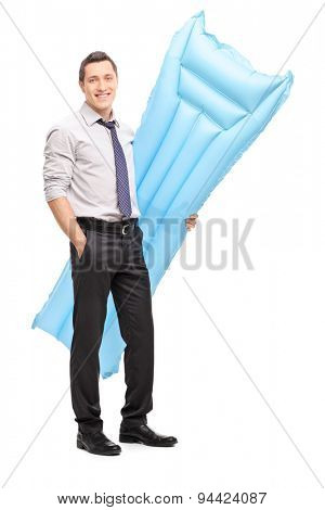 Full length portrait of a young businessman holding a blue swimming mattress and looking at the camera isolated on white background
