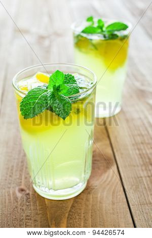 Two Glasses Of Drink With Lemon And Fresh Mint On Wooden Table.