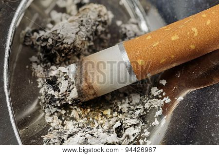 Cigarette And Ashes In A Metal Ashtray