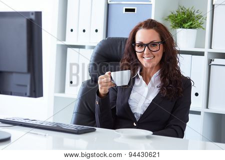Young Business Woman Drinks Coffee In Office