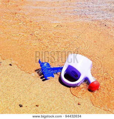 Children rack  and purple watering can on the sand