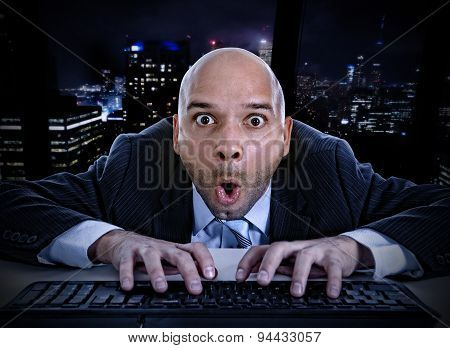Businessman Late At Night In Office Typing On Computer Keyboard With Funny Face Expression On Watchi