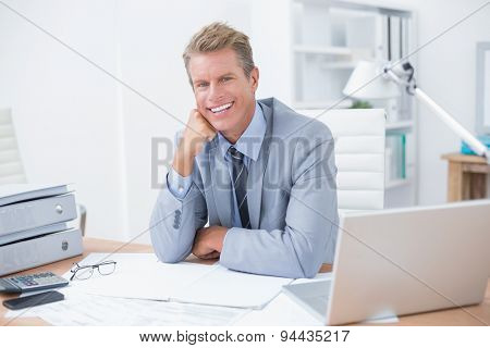 Very happy businessman at work in his office
