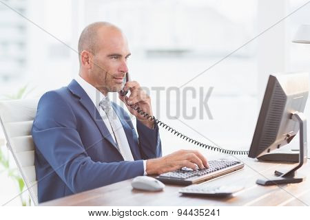 Businessman on the phone and using his computer in his office