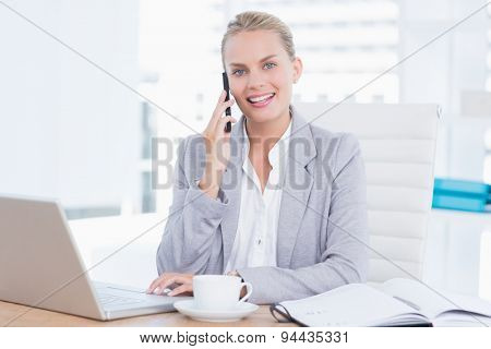 Smiling businesswoman using her computer in her office