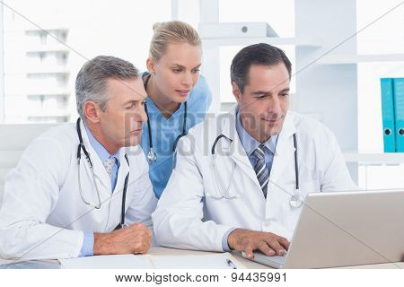 Doctors and nurse working with computer in medical office