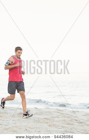 Handsome fit man running at the beach