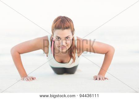 Beautiful brunette doing push ups at the beach