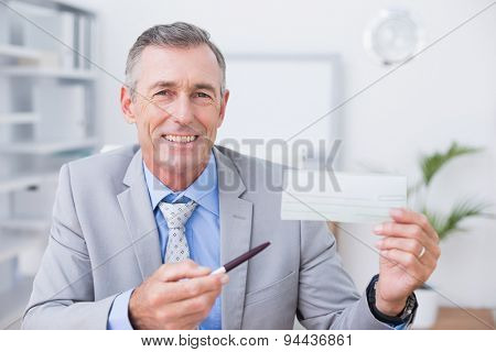 Smiling businessman holding cheque in his office