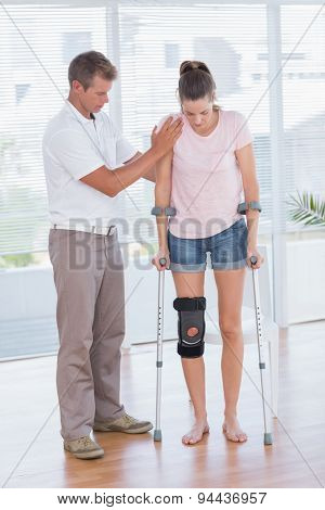 Doctor helping his patient walking with crutch in medical office