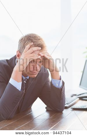 Businessman with his hand on his forehead in his office