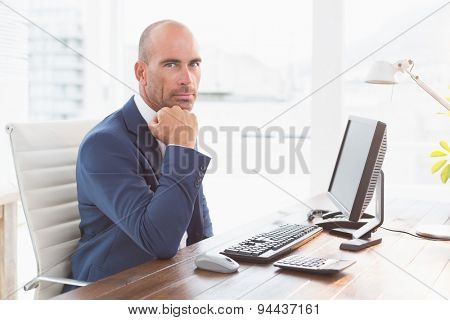 Businessman looking at camera at his desk in his office