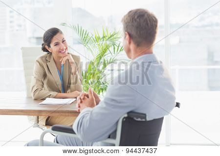 Smiling businesswoman interviewing disabled candidate in an office