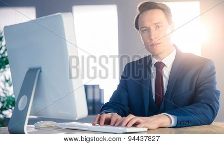 Confident businessman typing on computer and looking at camera in his office
