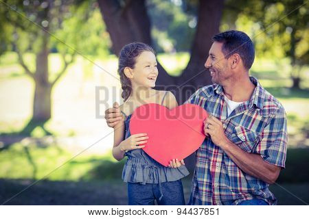 Father and daughter holding a heart in the park on a sunny day
