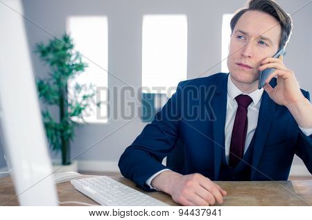 Serious businessman having a phone call in his office