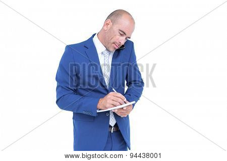 Young businessman writing on a notepad against white background