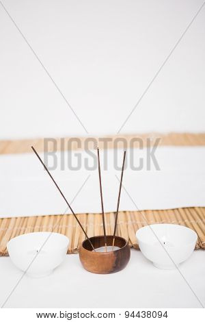 Perfumed candles and incense stem nearby a bamboo mat