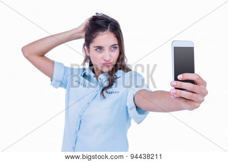 Pretty brunette taking a selfie with smartphone on white background