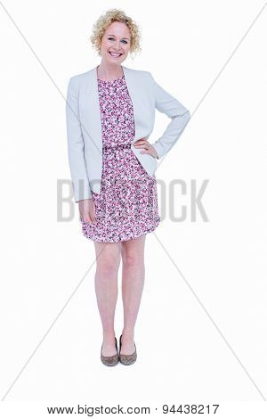 Pretty hipster with hand on chin smiling at camera on white background
