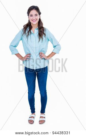Pretty hipster with hands on hips smiling at camera on white background