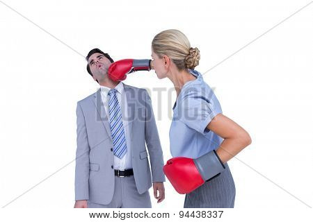Businesswoman punching colleague with boxing gloves on white background