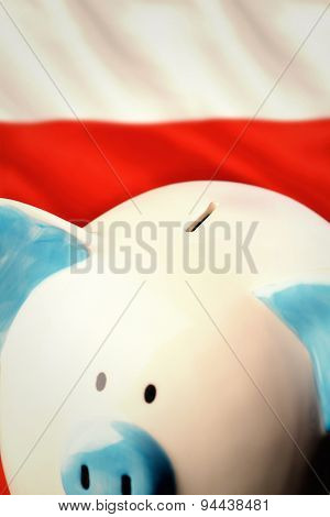 Piggy bank against digitally generated polish flag rippling