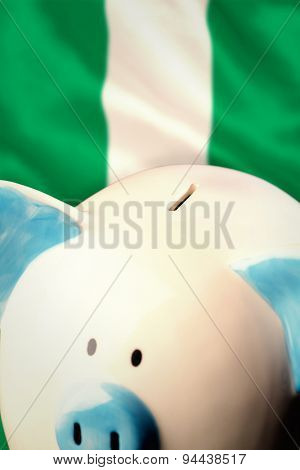 Piggy bank against digitally generated nigerian national flag