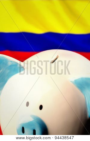 Piggy bank against digitally generated colombia national flag