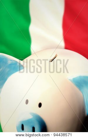 Piggy bank against digitally generated italian national flag