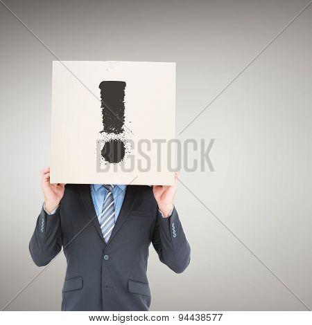 Businessman hiding head with a box against grey vignette