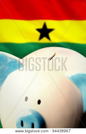 Piggy bank against digitally generated ghana national flag