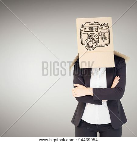 Businesswoman lifting box off head against grey vignette