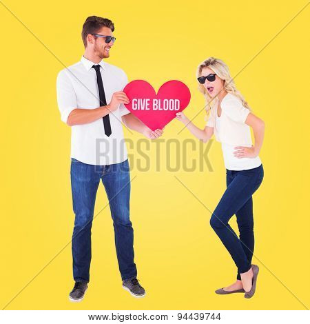 Cool young couple holding red heart against yellow vignette