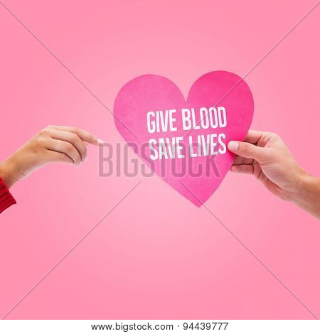 Couple holding a heart against pink