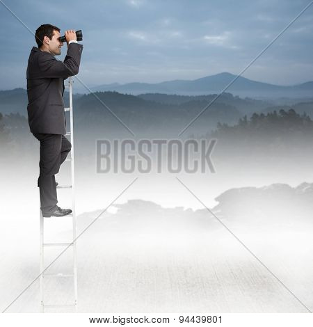 Businessman standing on ladder against misty forest