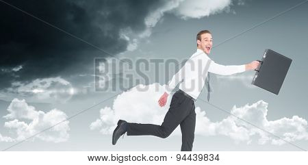 Happy businessman leaping with his briefcase against blue sky