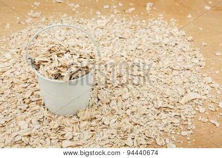 White Bucket With Oat Flakes  On The Wooden Floor