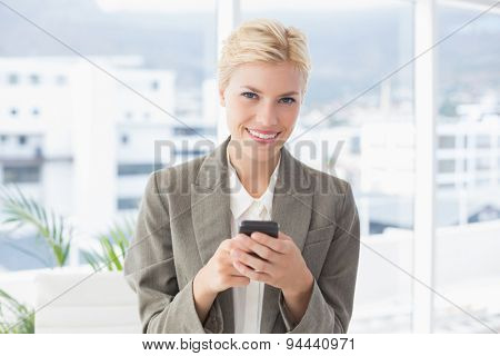 Businesswoman looking at camera and using her smartphone in an office