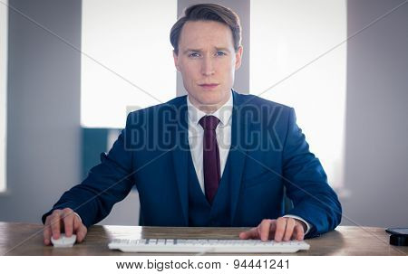 Serious businessman looking at camera in the office