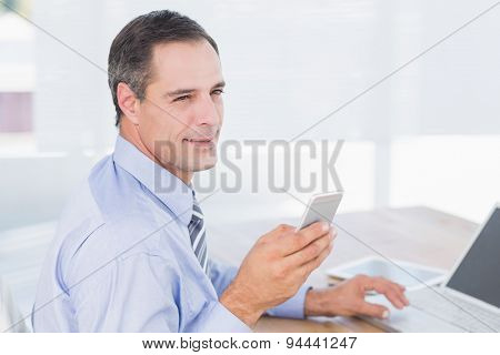Smiling businessman sending a text at his desk in his office