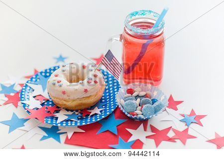 american independence day, celebration, patriotism and holidays concept - close up of glazed sweet donut with flag and candies in disposable tableware at 4th july party